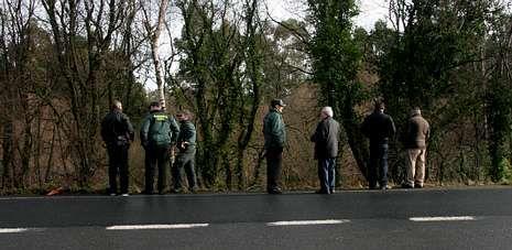 3.El padre del desaparecido (tercero por la derecha), junto a guardias civiles y vecinos ante el lugar donde apareció el coche accidentado.