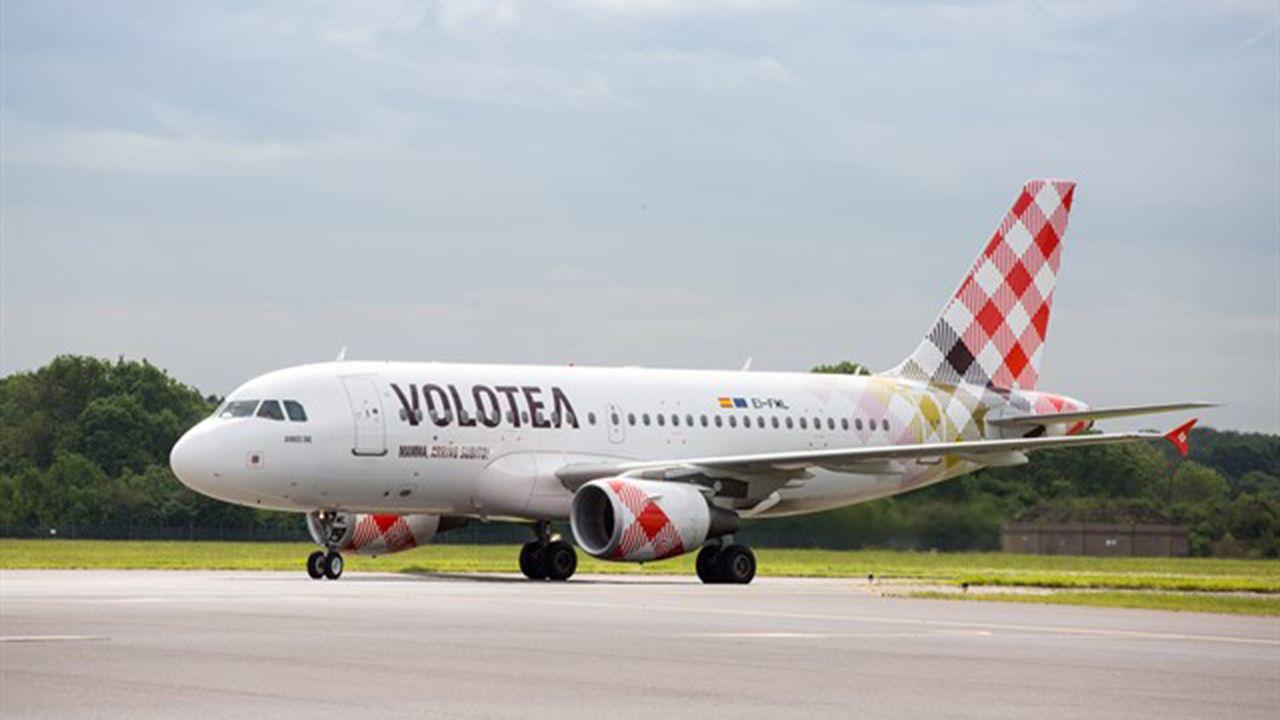 Un grupo de pasajeros consulta los vuelos en el Aeropuerto de Asturias.Un avión de Volotea