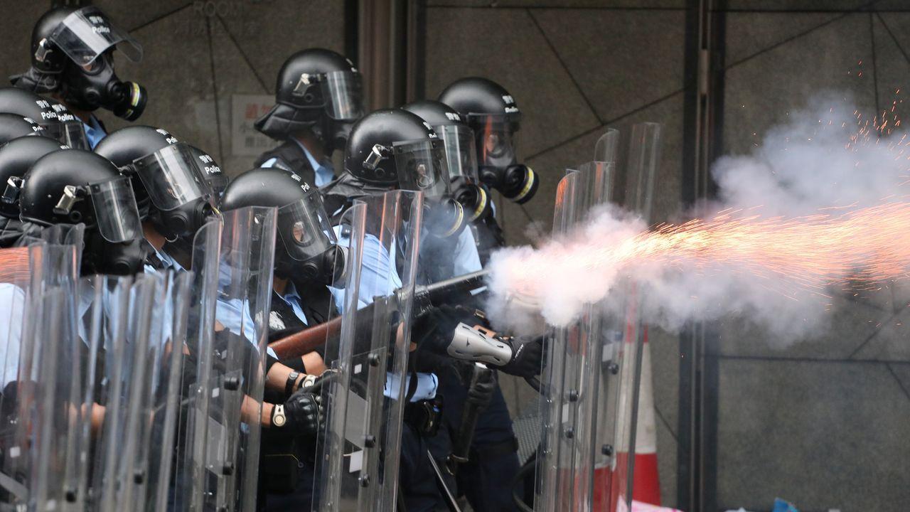 Los angentes antidisturbios lanzan gases lacrimógenos contra los congregados en el centro de la ciudad