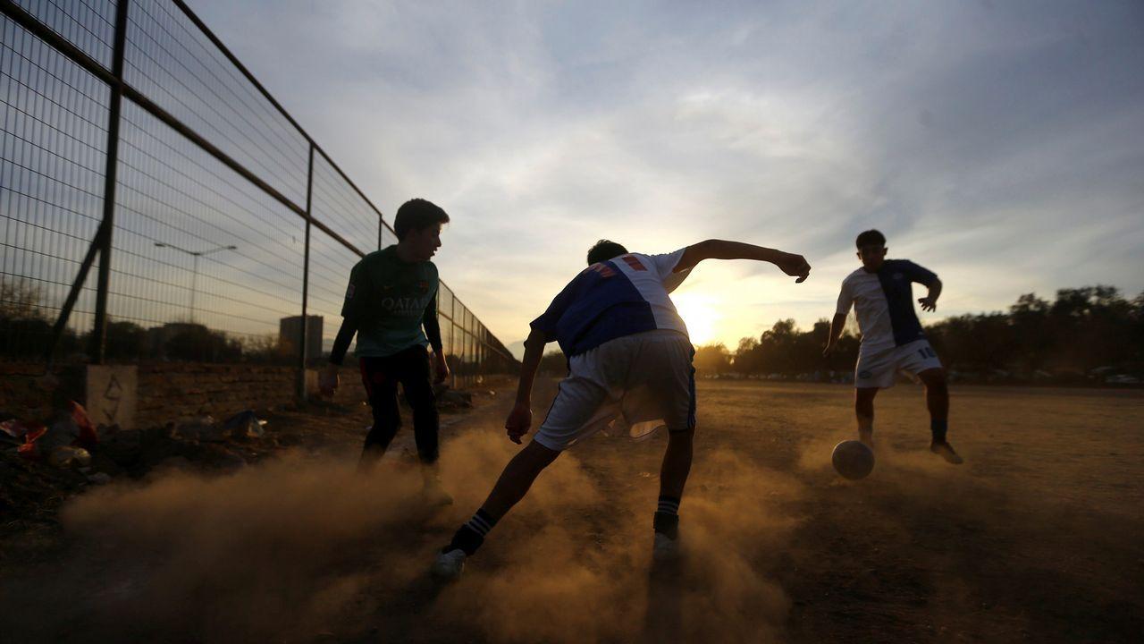 .Un grupo de jóvenes juega al fútbol en Santiago de Chile