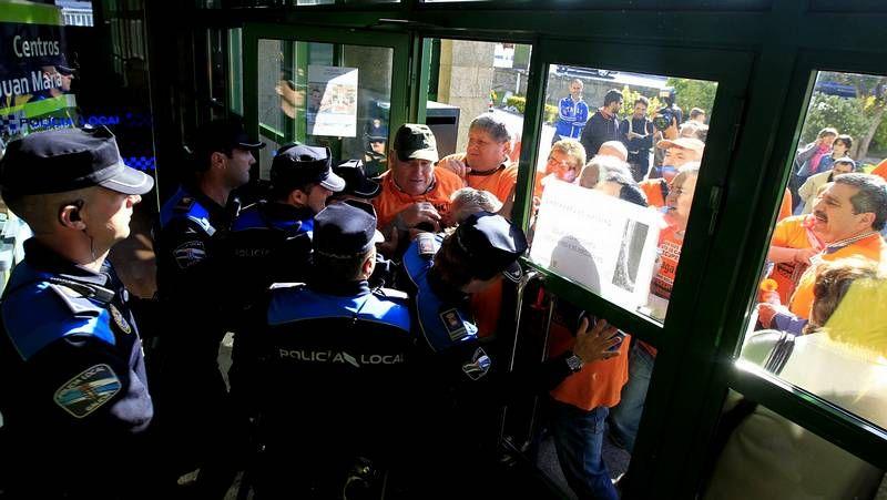 Agentes de la Policía Local de Nigrán cerrando la entrada al Concello a un concurrido grupo de afectados por las preferentes.