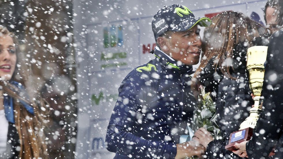 El colombiano Nairo Quintana (c), del Movistar, en el podio del Alto del Acebo, de 1.200 metros de altitud, donde está nevando, tras ganar la segunda etapa de la 60 Vuelta Ciclista a Asturias, disputada entre Soto de Rivera y Cangas del Narcea.
