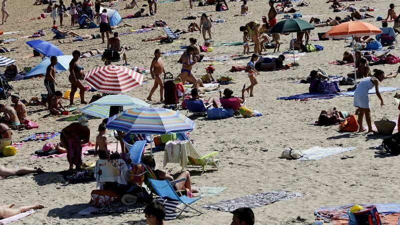 La «tardía» ola de calor achicharra Galicia.El intenso calor de ayer permitió disfrutar de la playa en el norte de la comunidad mientras en las Rías Baixas caía la niebla.