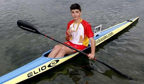 .Xoel García posa coa súa medalla na piragua coa que competiu.