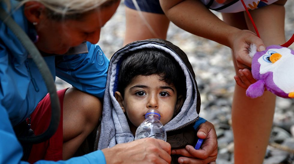 Miles de refugiados siguen bloqueados en la frontera entre Croacia y Serbia.Una voluntaria ofrece agua a un niño sirio exhausto recién desembarcado en Lesbos.