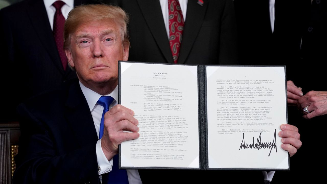 .El presidente estadounidense Donald Trump sostiene el memorando que ha firmado sobre aranceles de propiedad intelectual a los productos de alta tecnología procedentes de China en la Casa Blanca