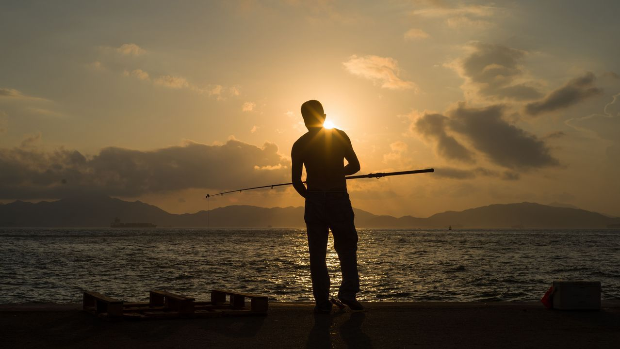 .Un hombre  camina con su caña de pescar por el puerto de Hong Kong