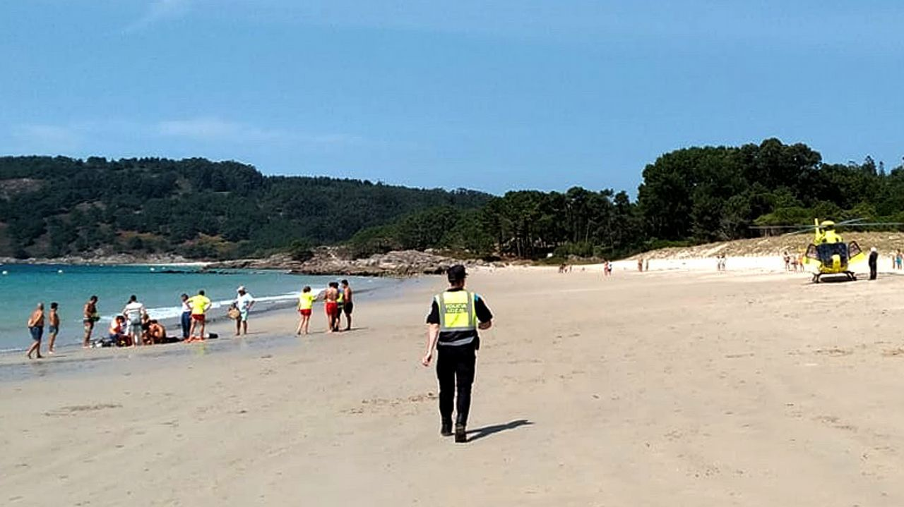 El top 10 de las playas gallegas en Instagram.Una bañista se protege del vientro detrás de una piedra en la playa de Xagó (Gozón)