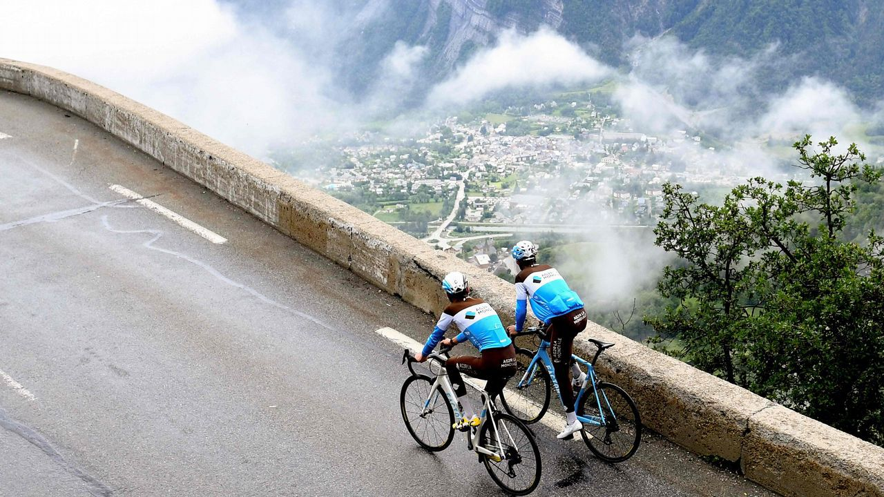 Dos ciclistas del equipo AG2R pasan frente al Alpe d'Huez