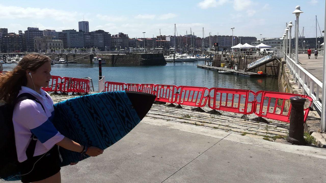.Una valla cierra el acceso a una de las rampas del Puerto Deportivo mientras al fondo se celebra el acto de izado de la Bandera Azul