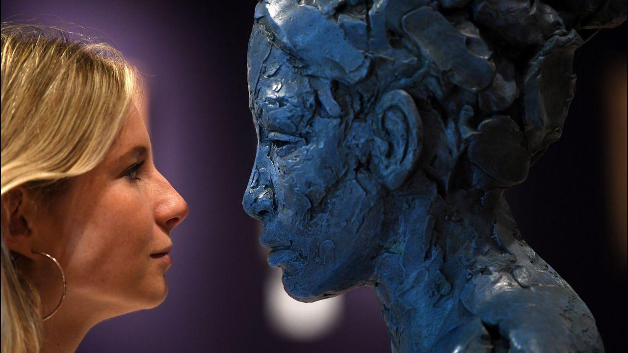 Una empleada observaunla escultura del artista sudafricano Lionel Smit, en Londres