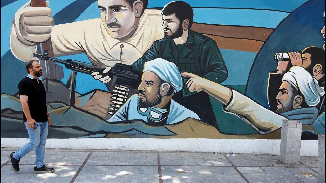 Un hombre pasa delante de uno de los murales belicosos que inundan las calles de Teherán