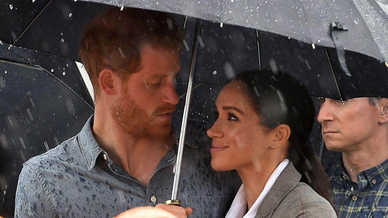 Polémica en Reino Unido por la imagen de Meghan Markle tapando con su paraguas al príncipe Harry