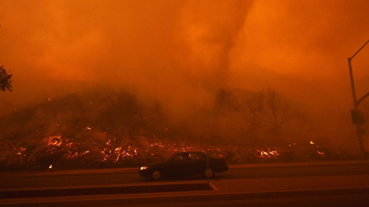 Un automóvil atraviesa un vecindario residencial después de que el fuego derribara una ladera durante el Fuego Sagrado en Lake Elsinore, California, al sureste de Los Angeles
