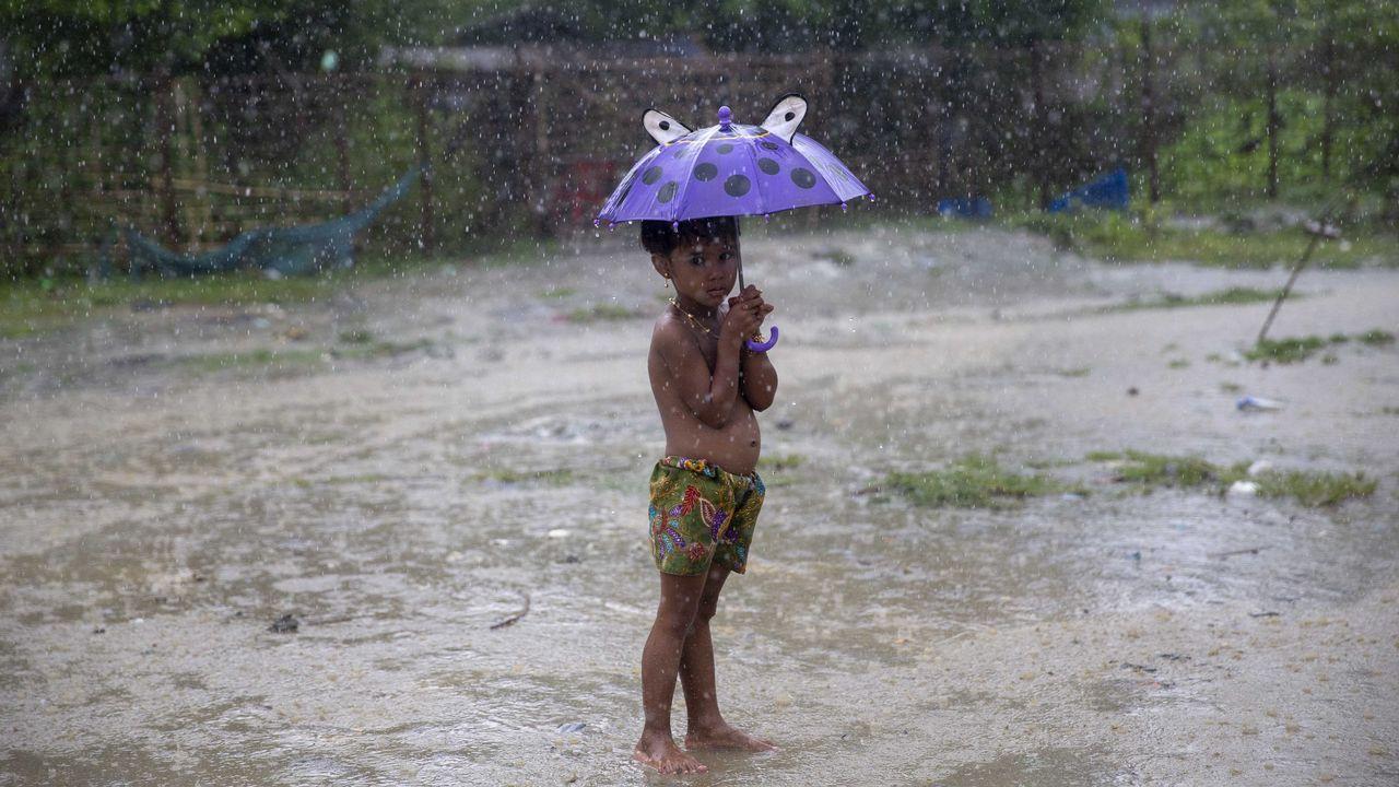 Un niño musulmán rohingya sosteniendo un paraguas bajo la lluvia en la aldea de Shwe Zar es fotografiado durante una visita organizada por el gobierno para periodistas en el municipio de Maungdaw, estado de Rakhine
