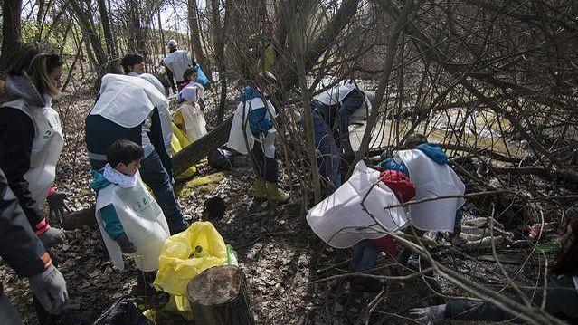 Colectivos asturianos limpiando la basura en las zonas aledañas a un río