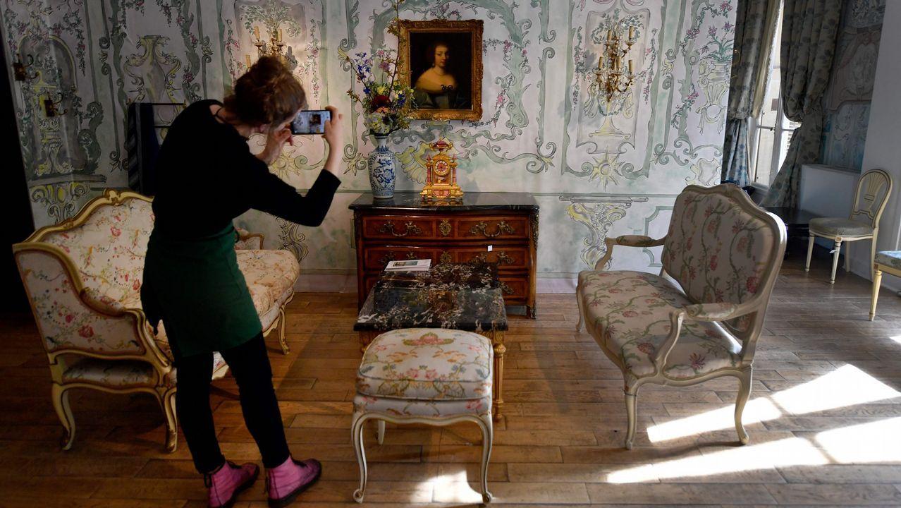 Una mujer toma una fotografía de uno de los salones del hotel donde se exhiben los lotes que saldrán a subasta