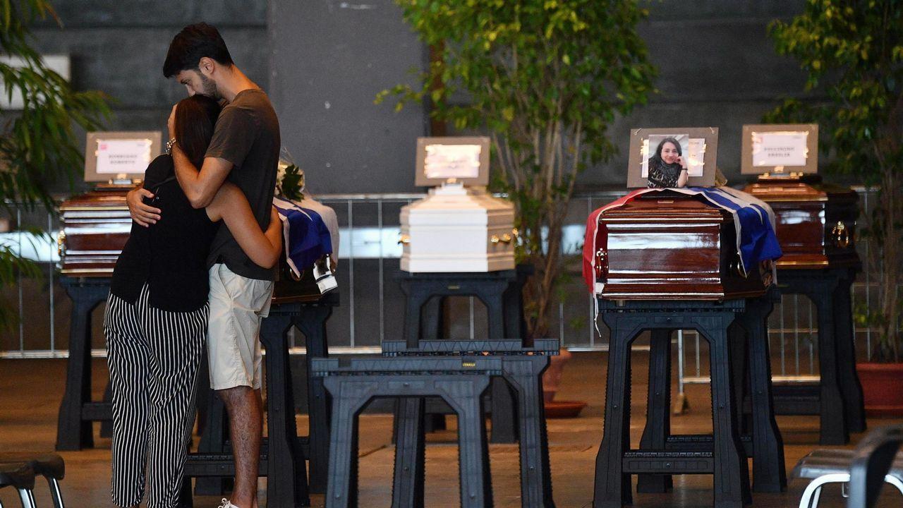 .Familiares de las víctimas del derrumbe del viaducto en Génova se abrazan frente a los féretros de algunos de los fallecidos