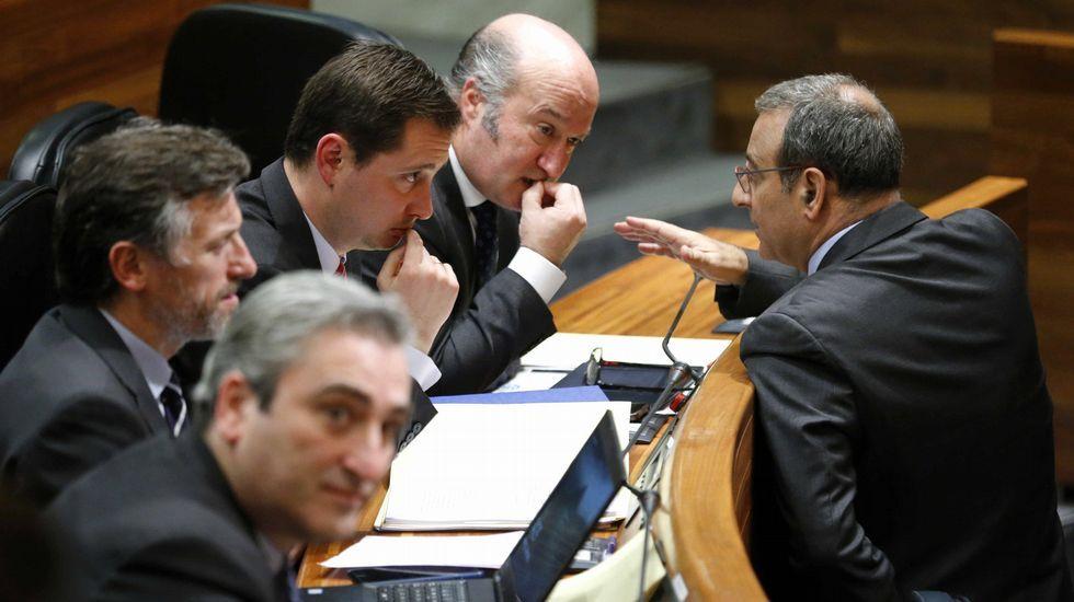 El portavoz de Podemos, Emilio León, interviene en la Junta General ante la mirada de Javier Fernández y Guillermo Martínez. El consejero de Infraestructuras, Fernando Lastra (d), y el diputado popular, Luis Venta (2d), conversan durante el pleno de hoy de la Junta General