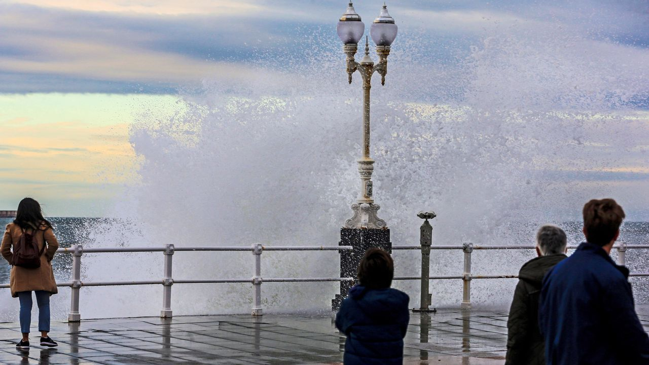 Varias personas observan las olas en el Muro de San Lorenzo de Gijón, donde el temporal marítimo de los últimos días ha provocado daños valorados en 15.916 euros, según los técnicos de obras públicas del Ayuntamiento