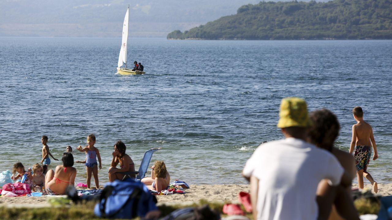 Bañistas en la playa del lago de As Pontes