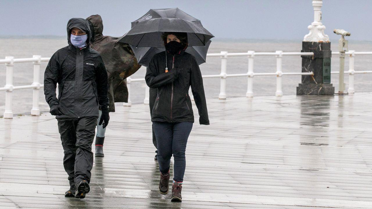 Contaminación en Gijón.Un grupo de personas pasea por la playa de San Lorenzo de Gijon, bajo la lluvia y el viento