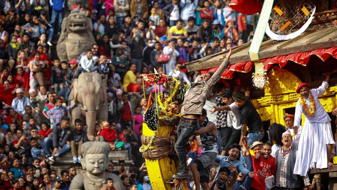 Devotos nepaleses empujan un carro de madera que porta al dios Bhairab, mientras participan en el tradicional festival Bisket Jatra, con motivo de las celebraciones del año nuevo nepalí en la comunidad newar, cerca de Katmandú (Nepal)