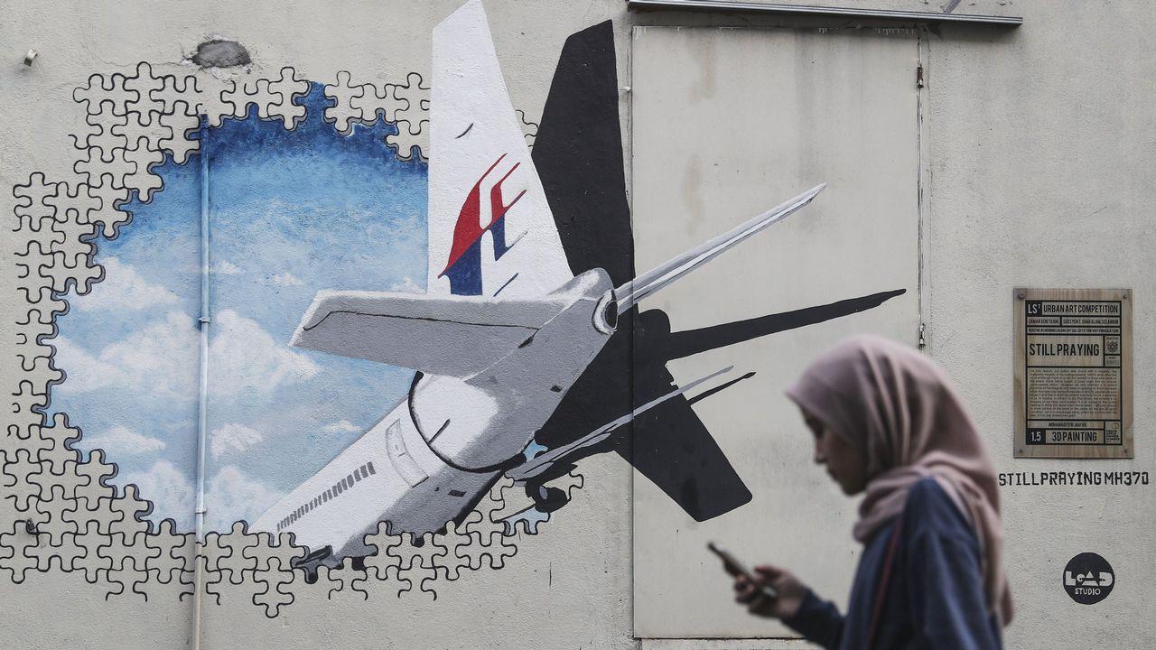 .Una mujer pasea frente a un mural sobre el vuelo MH370 de Malaysia Airlines en Shah Alam, a las afueras de Kuala Lumpur