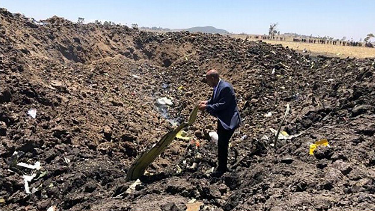 Un hombre inspecciones el lugar del accidente, en Bishoftu, 60 kilómetros al sureste de Addis Abeba, Etiopía