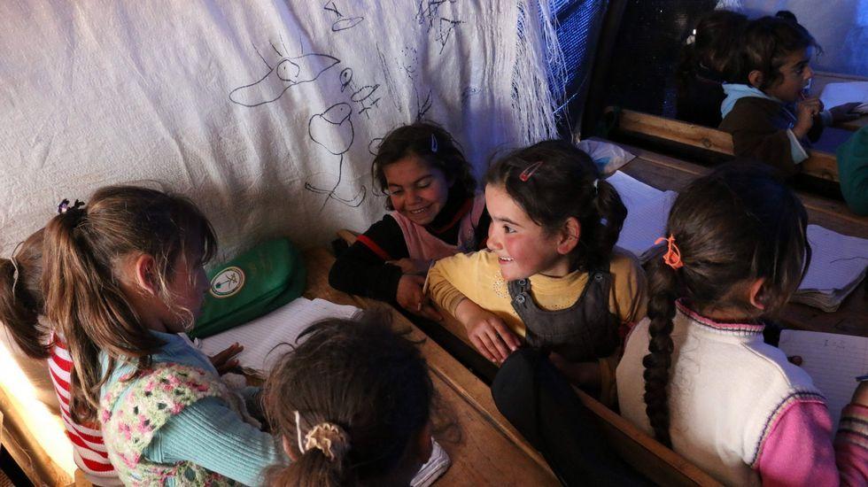 .Nenas sirias desprazadas nun campamento para refuxiados asisten a clase