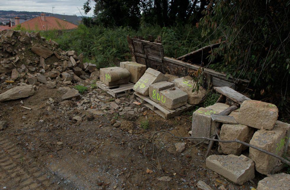 Las piedras de un marco desmontado permanecen amontonadas junto al vial de acceso.