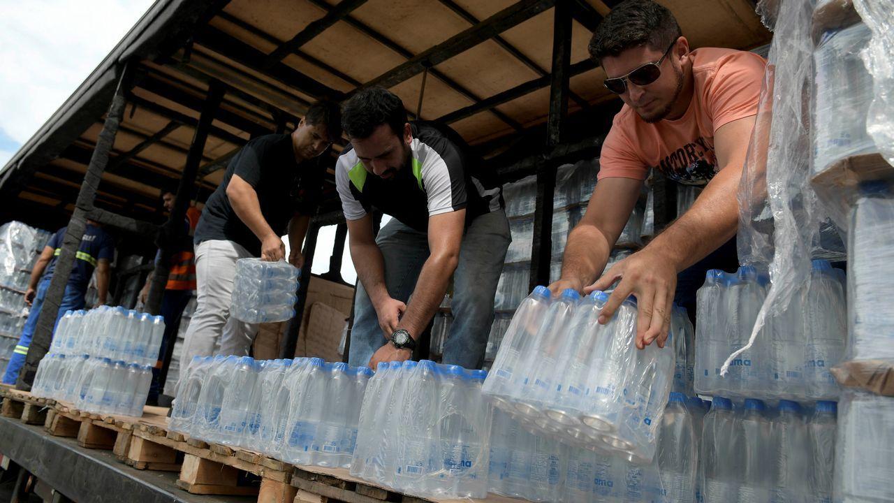 Voluntarios reparten botellas de agua para las personas afectadas después de que la presa de desechos tóxicos de mineral de hierro fallase
