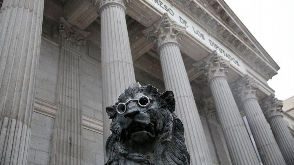Plena inclusión con los partidos políticos.Uno de los dos leones que cusjtodian la entrada al Congreso de los Diputados en Madrid, caracterizado con unas gafas, en honor a los 400 años del fallecimiento de Miguel de Cervantes.
