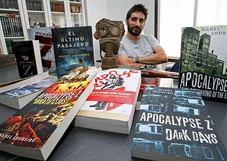 .Manel Loureiro rodeado de sus libros, y una máscara de gas alemana que tiene en su despacho.