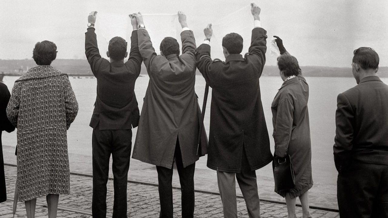 Un grupo de familiares despiden a emigrantes no porto da Coruña no ano 1957, nunha das imaxes máis icónicas da exposición «Os adeuses»