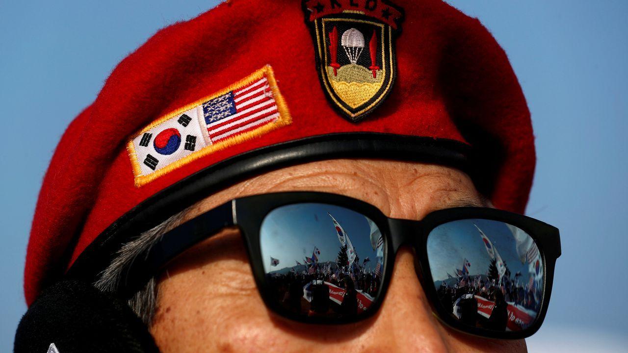 Los manifestantes se reflejan en las gafas de otro manifestante durante una protesta contra Corea del Norte antes de la ceremonia de inauguración de los Juegos Olímpicos de Invierno