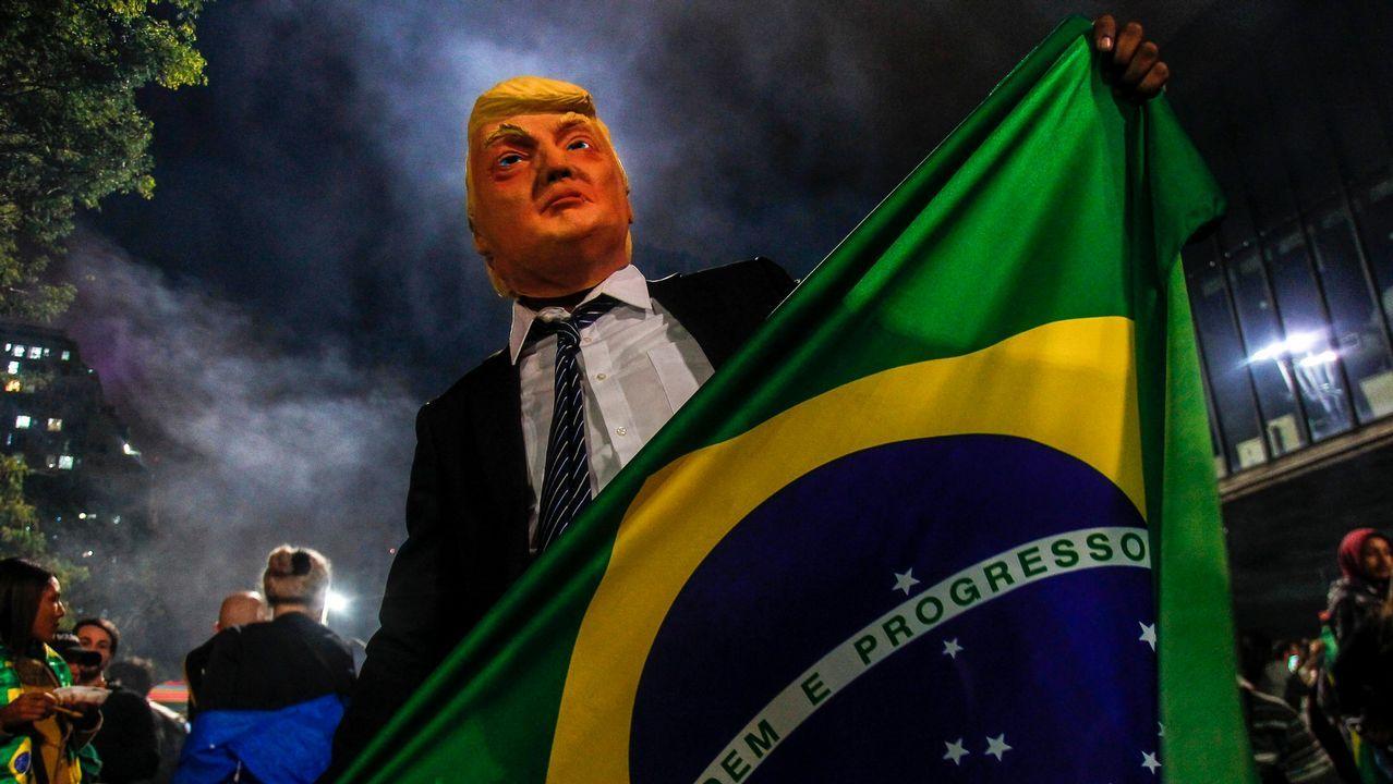 Un seguidor de Bolsonaro disfrazado de Trump sostiene una bandera de Brasil