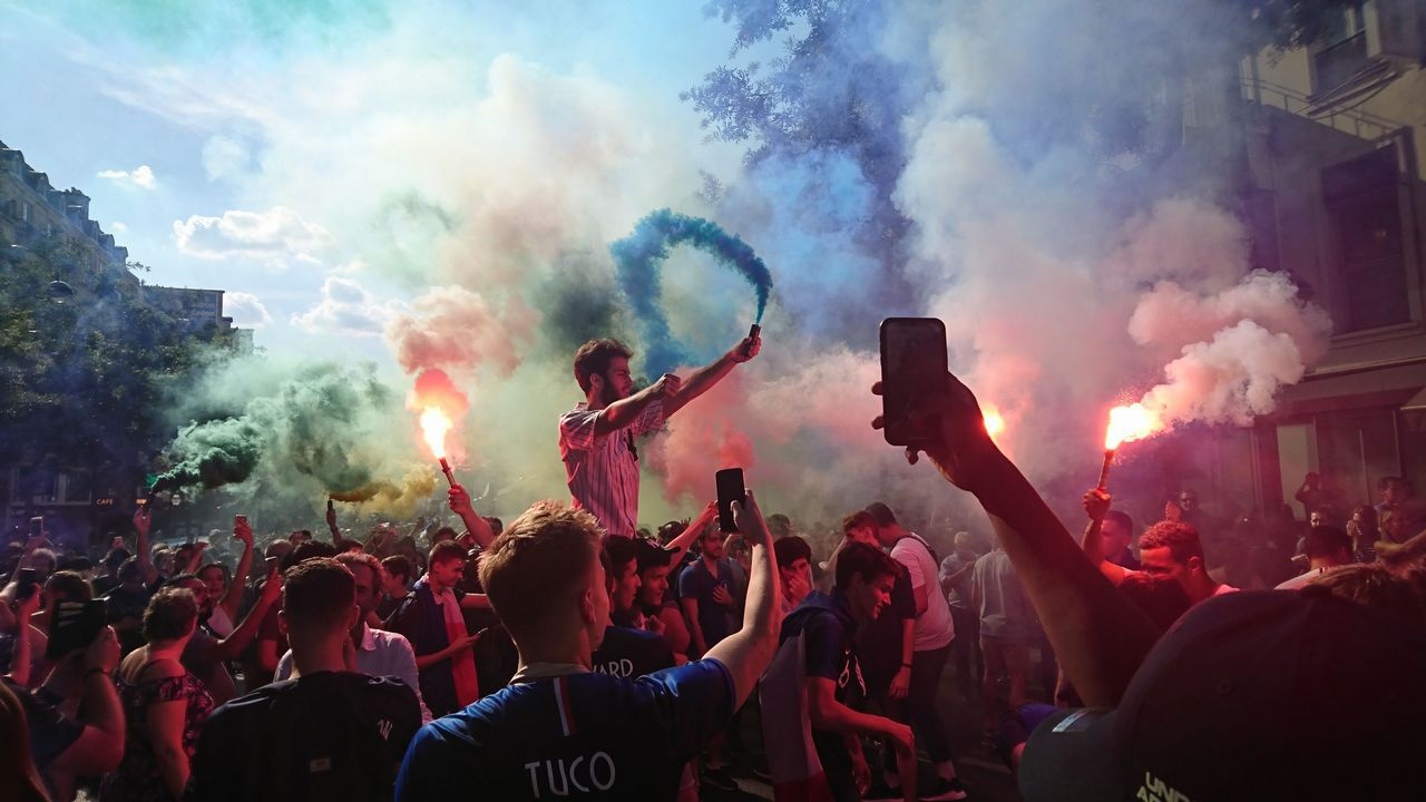 .Aficionados franceses sostienen bengalas mientras celebran la victoria de su selección en el Boulevard Poissoniere en París