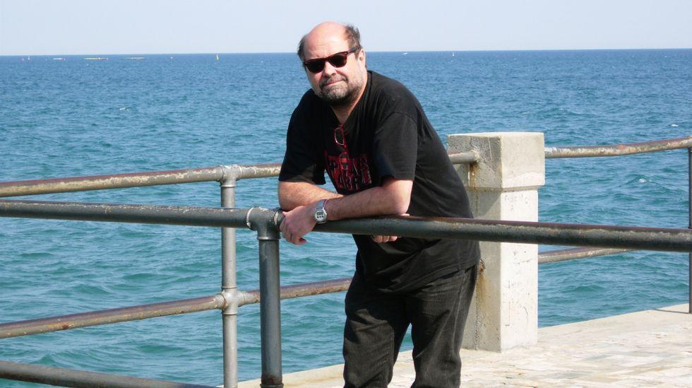 José Luis Goldar Díaz, ayer, con una foto de su padre en la taberna O Muíño de Caldas, situada a orillas del río Umia.