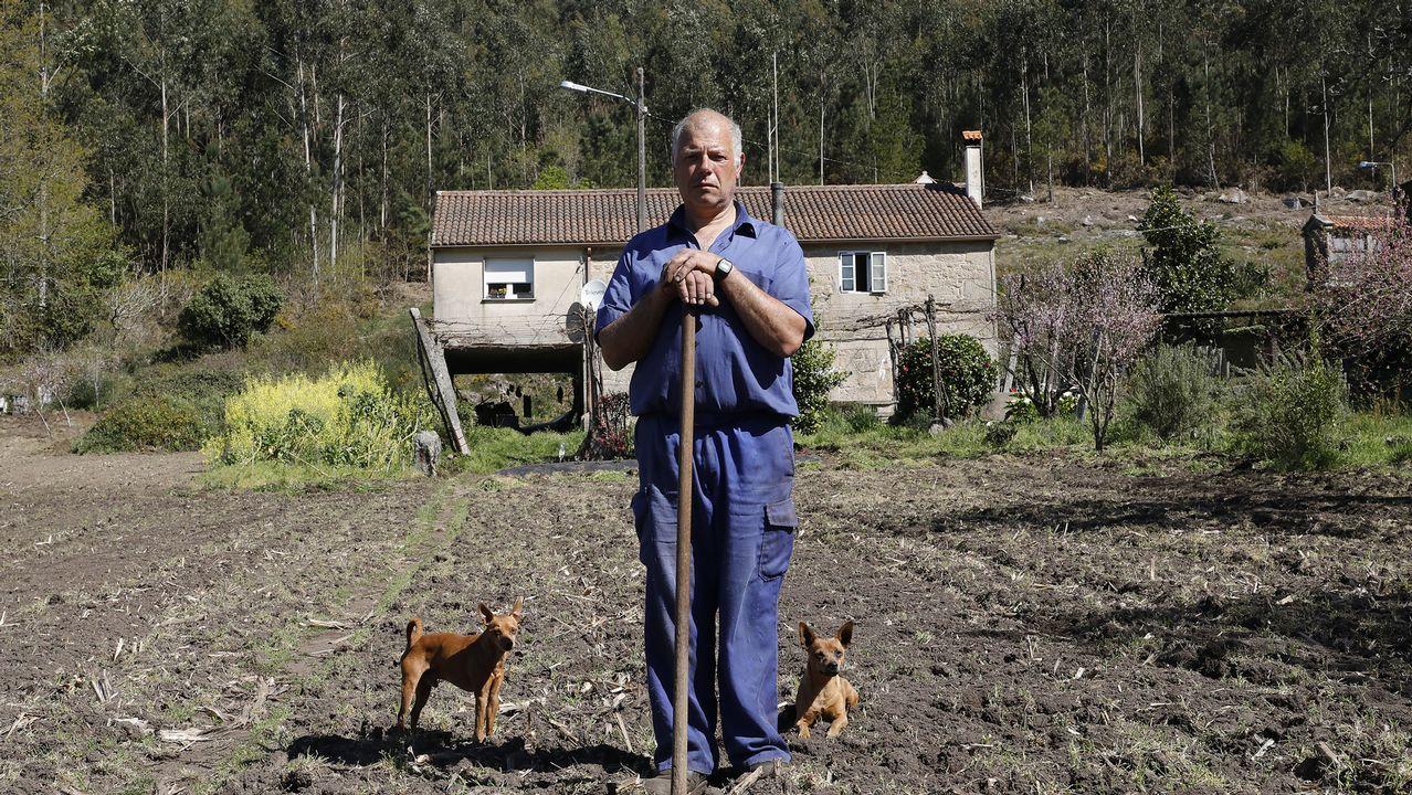 José Martínez, escoltado por sus perras Lana y Nani, posa frente a su casa, en Confurco
