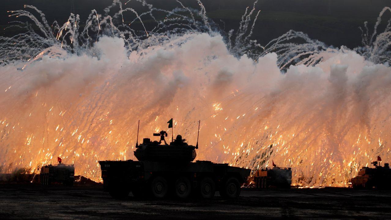 Tanques militares y vehículos armados de las Fuerzas terrestres de Autodefensa niponas (JGSDF) disparan bengalas para crear una pantalla de humo durante unas maniobras militares en los campos de entrenamiento de Higashi Fuji, cerca del Monte Fuji, en Gotemba, Japón