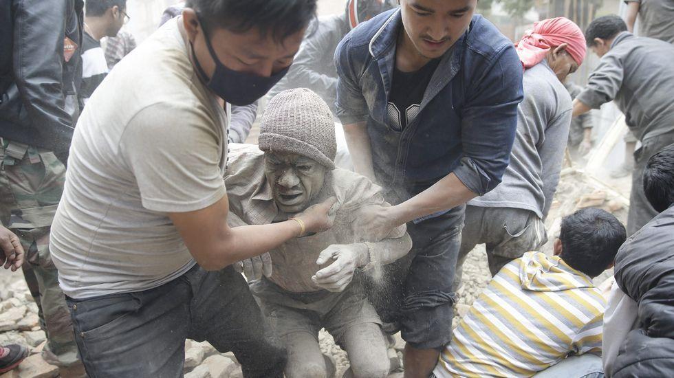 Dos hombres tratan de liberar a un hombre tras un derrumbe en Katmandú.