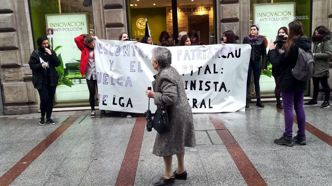 Manifestantes feministas ante un comercio de la calle Corrida de Gijón en la huelga general del 8-M