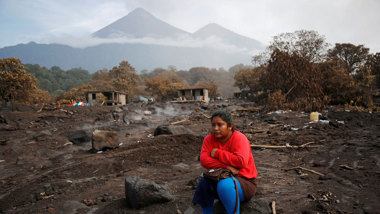 .Una mujer observa el lugar donde cree que fueron sepultados sus hermanos, en la zona afecta por la erupción del volcan Fuego, en Guatemala
