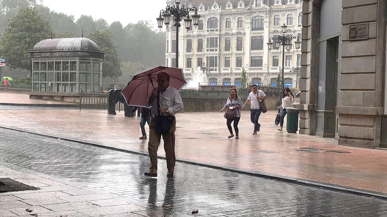 .Los peatones se protegen de las lluviosas tormentas de verano que cayeron sobre Oviedo