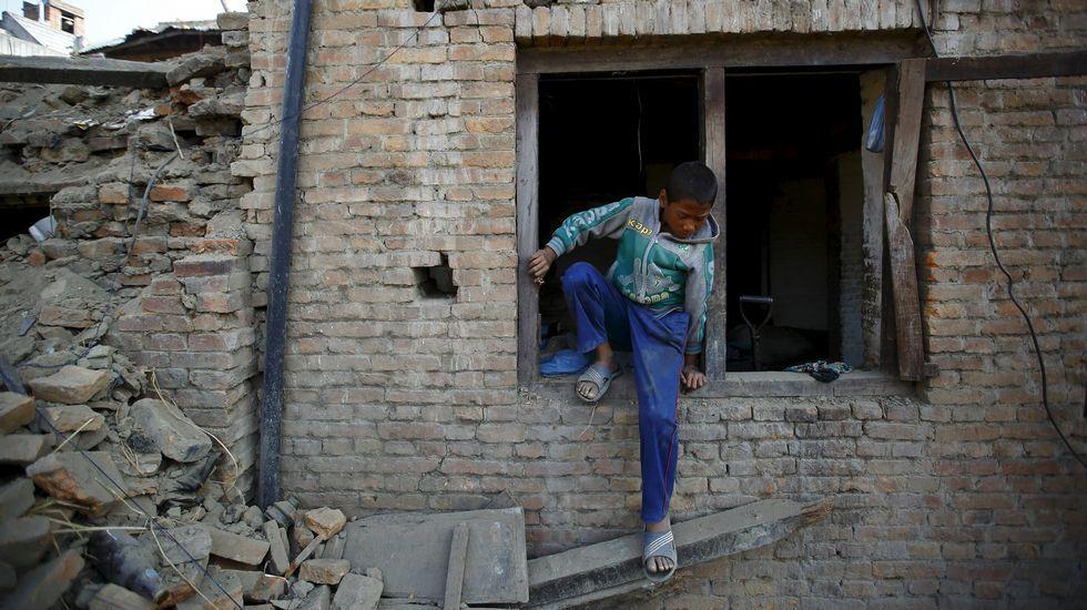 Un niño sale por la ventana de su casa en Katmandú.