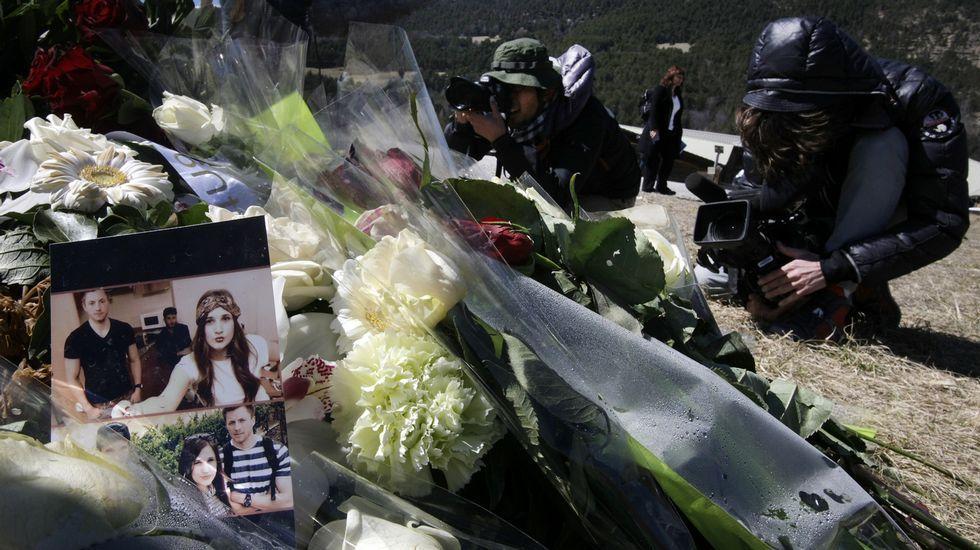 .Periodistas toman imágenes de las flores y las fotos que se amontonan ante el monolito en homenaje a las víctimas, en Le Vernet.