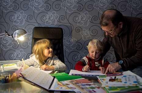.Un adulto ayuda a sus hijos a realizar los deberes en su domicilio.