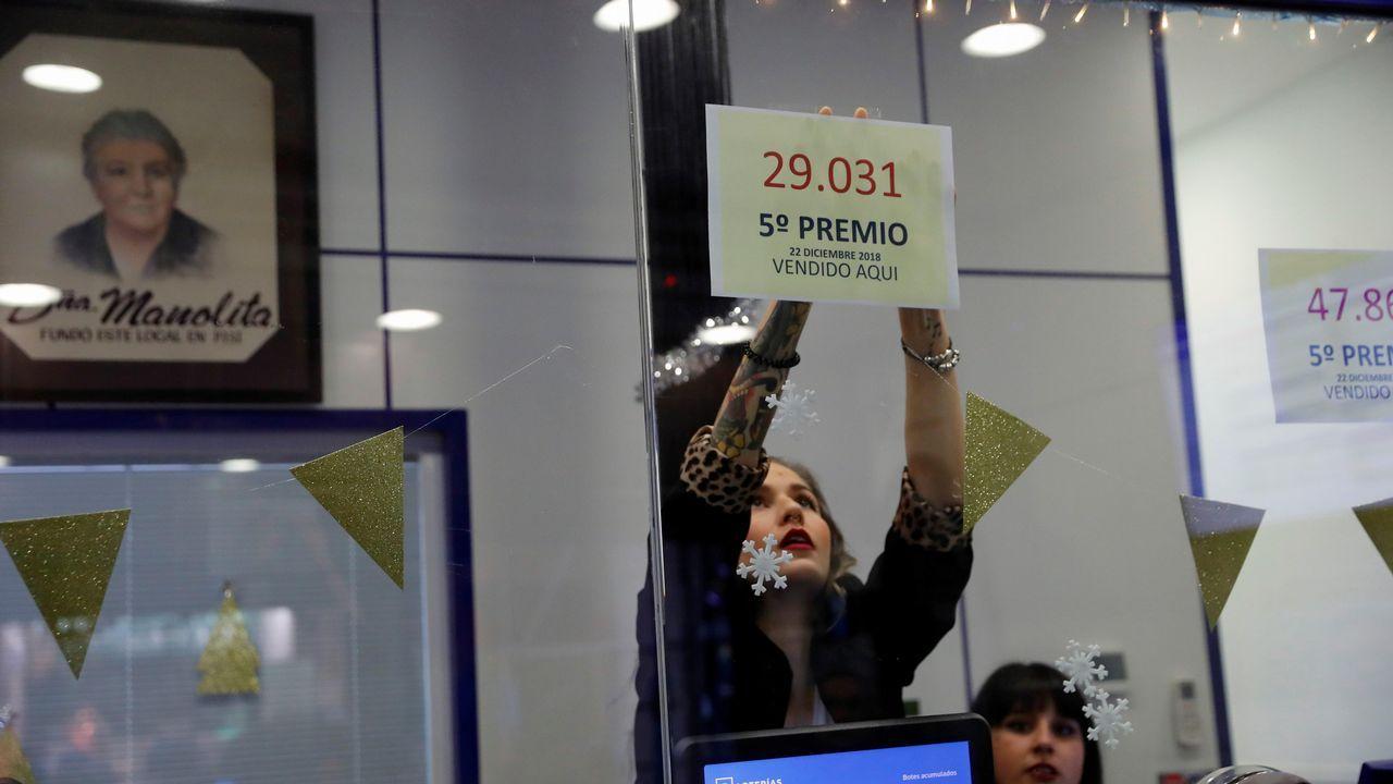 Una empleada de la administración de Loteria de «Doña Manolita», en la madrileña calle Carmen 22, coloca uno los números correspondientes a los tres quintos premios del sorteo Extraordinario de la lotería Navidad dotado con 60.000 euros a la serie cada uno
