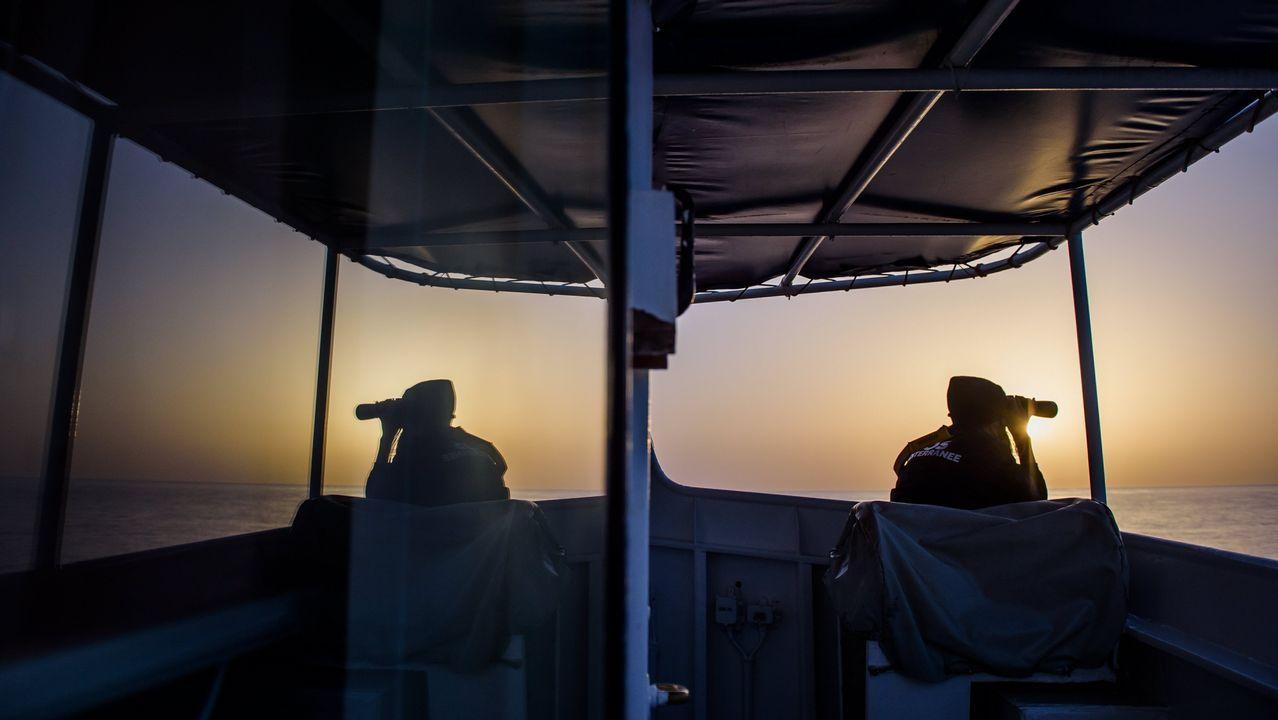 .Un miembro de la ONG SOS Mediterráneo observa el horizonte con unos prismáticos